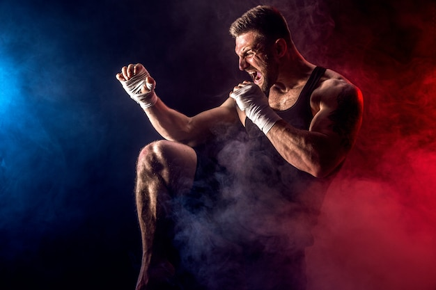 Deportista muay thai boxeador luchando en la pared negra con humo.