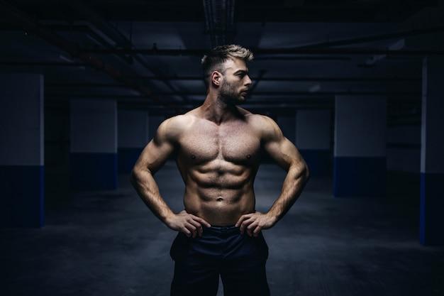 Deportista musculoso caucásico sin camisa guapo joven de pie con las manos en las caderas en el garaje por la noche y mirando a otro lado. concepto de vida urbana.