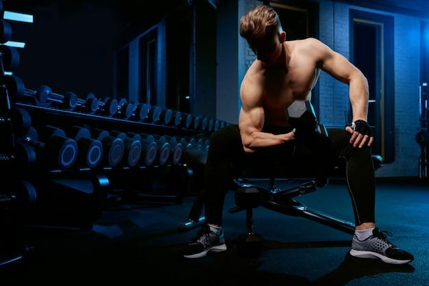 Deportista musculoso entrenamiento brazos con mancuernas.