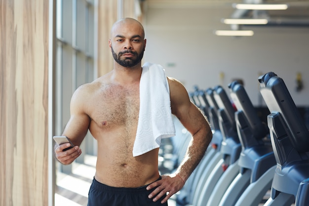 Deportista musculoso mirando a cámara en el gimnasio