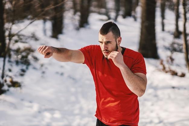 Deportista musculoso sparring en bosque nevado en invierno. boxeo en la naturaleza, deportes de invierno, fitness en la naturaleza