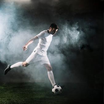 Deportista pateando el balón de fútbol en el humo