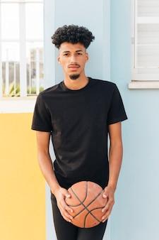 Deportista de pie con el baloncesto y mirando a la cámara