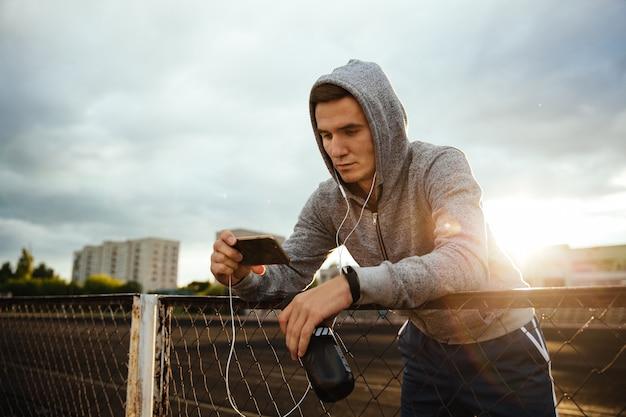 Deportista de pie usando la aplicación mientras bebe agua, escuchando música