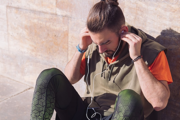 Deportista poniéndose auriculares para escuchar música