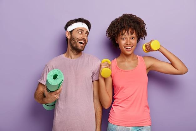 Deportista positivo usa diadema y camiseta, sostiene una alfombra de fitness arrugada, mira con alegría a la novia que levanta los brazos con pesas, hacen ejercicio juntos