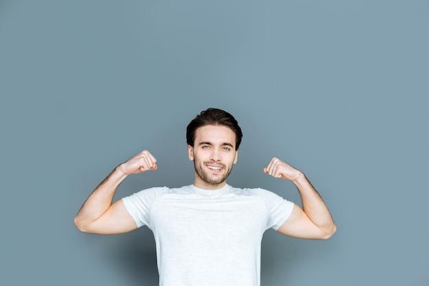Deportista profesional. encantado de buen hombre atlético sonriendo y mirándote mientras muestra su fuerza