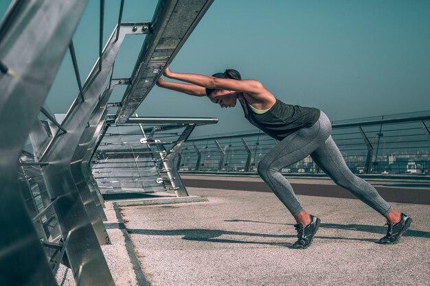Deportista profesional entrenando en el puente y estirando su cuerpo por la barandilla