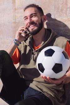 Deportista riendo y hablando por teléfono