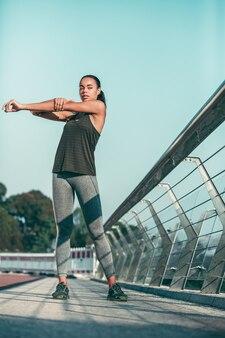 Deportista seria en el puente calentando los músculos de sus hombros y brazos
