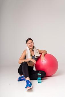 La deportista se sienta con una pelota de fitness y agua y una toalla sobre un fondo blanco y sonríe
