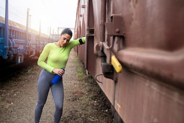Deportista tomando un descanso y apoyándose en el vehículo del tren después de un duro entrenamiento de carrera.