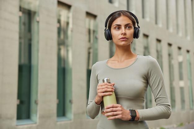 Deportista vestida con ropa deportiva sostiene una botella de agua recrea después de que el entrenamiento cardiovascular usa auriculares inalámbricos mira hacia otro lado posa cerca del edificio de la ciudad moderna