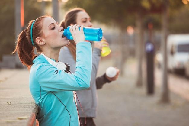 Deportistas cansadas bebiendo agua