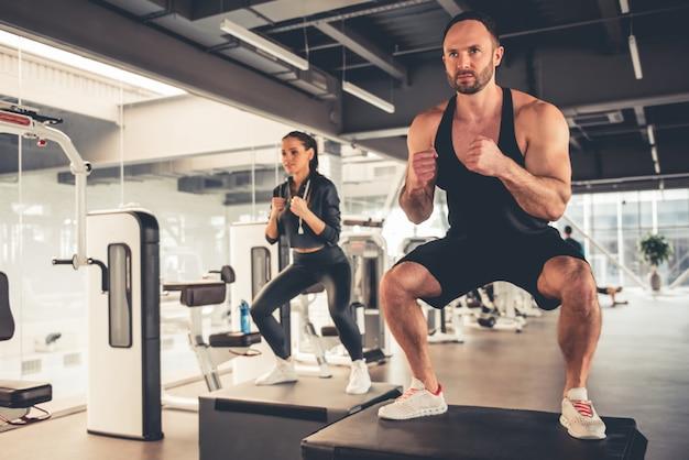 Los deportistas hacen saltos de caja mientras hacen ejercicio en el gimnasio.