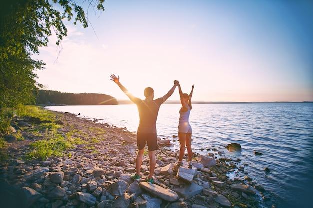 Deportistas levantando los brazos al aire libre