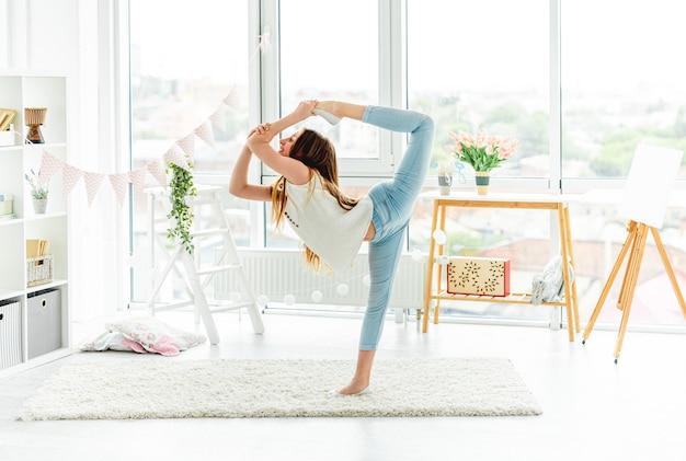 Deportiva adolescente realizando movimientos acrobáticos