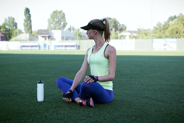 Deportiva chica bebiendo de una botella. estadio de fútbol. mujer delgada fitness deportivo. botella shaker protein. concepto de medios sociales y fitness.