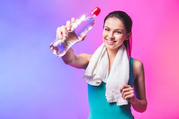 Deportiva chica con una botella de agua y una toalla sobre sus hombros. foto del modelo de fitness aislada sobre fondo blanco.