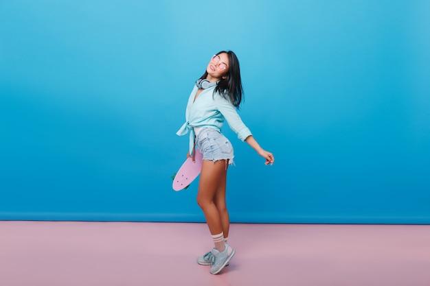 Deportiva chica hispana de pelo castaño en traje de mezclilla mirando hacia arriba. maravillosa chica latina en elegantes zapatos con longboard
