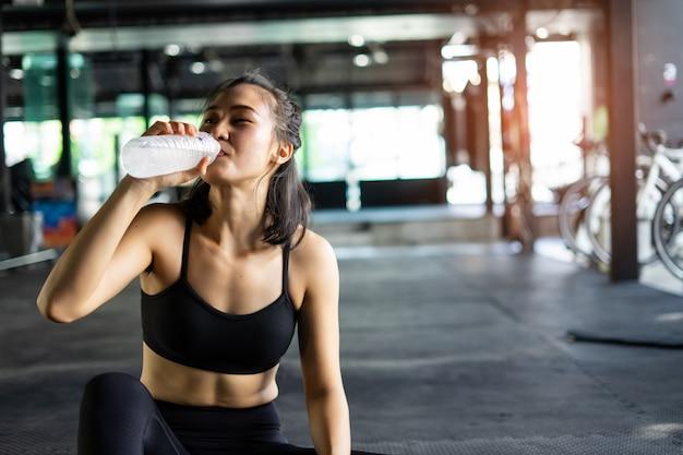 Deportiva hermosa mujer haciendo ejercicio, relájate y bebe agua con equipo de entrenamiento