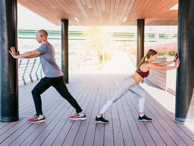 Deportiva hombre y mujer ejercitando juntos