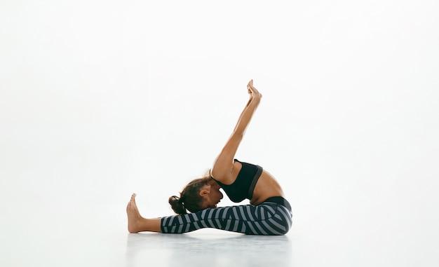 Deportiva joven haciendo práctica de yoga aislada en el espacio en blanco. colocar modelo femenino flexible practicando
