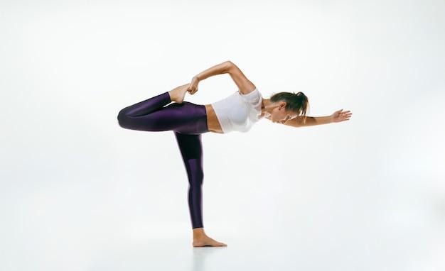 Deportiva joven haciendo práctica de yoga aislada en la pared blanca. ajuste el modelo femenino flexible practicando. concepto de estilo de vida saludable y equilibrio natural entre el cuerpo y el desarrollo mental.