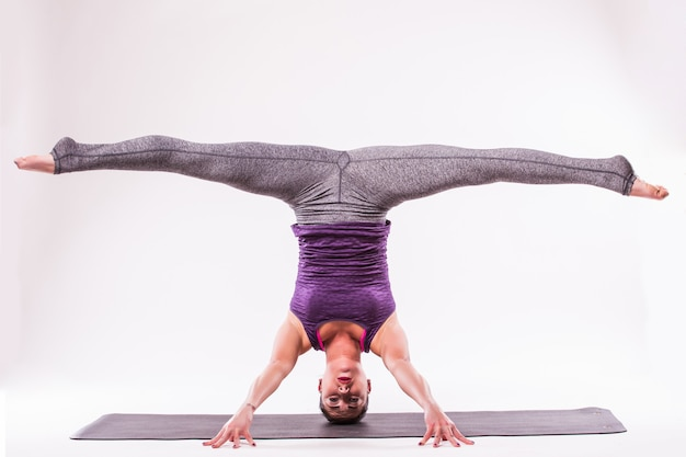 Deportiva joven haciendo práctica de yoga aislada sobre fondo blanco - concepto de vida sana y equilibrio natural entre el cuerpo y el desarrollo mental