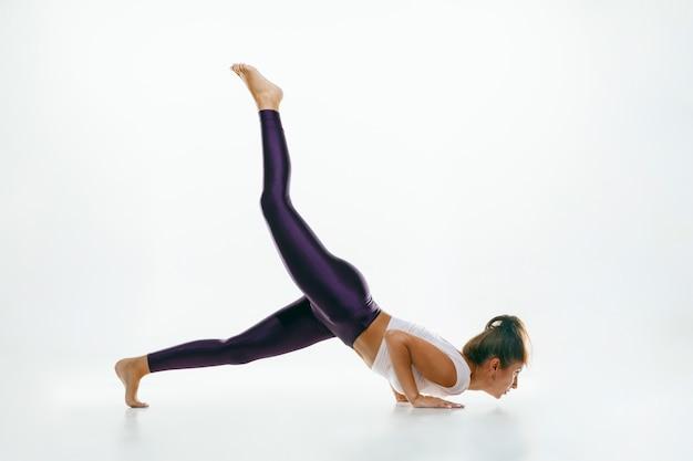 Deportiva joven haciendo práctica de yoga aislado en blanco