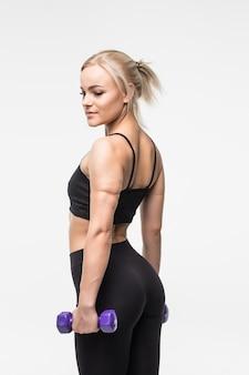 Deportiva joven rubia con cuerpo musculoso en forma trabaja con pesas en estudio en blanco