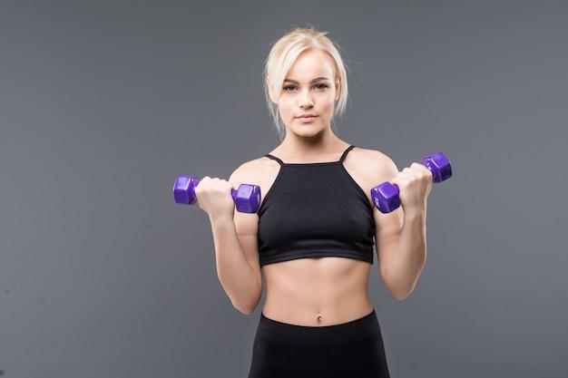 Deportiva joven rubia con cuerpo musculoso en forma trabaja con pesas en estudio en gris