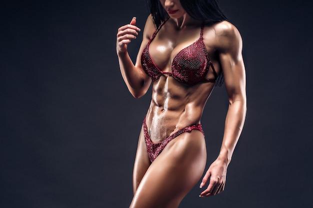 Deportiva jovencita bronceada sexy con grandes músculos abdominales