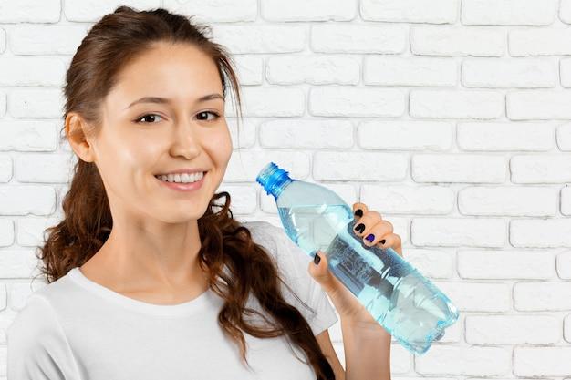 Deportiva mujer agua potable al aire libre en un día soleado