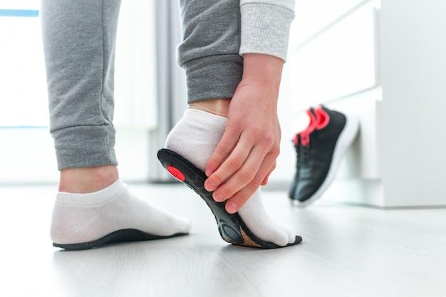 Deportiva mujer ajustando plantillas ortopédicas.