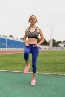 Deportiva mujer calentando antes de entrenar