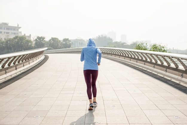 Deportiva mujer con capucha corriendo en puente