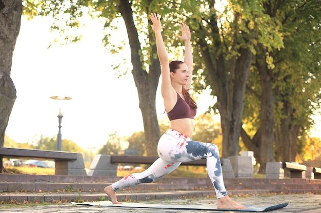 Deportiva mujer concentrada practicando yoga, de pie en pose anjaneyasana, ejercitándose en el parque al atardecer.