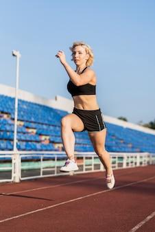 Deportiva mujer corriendo entrenando en el estadio