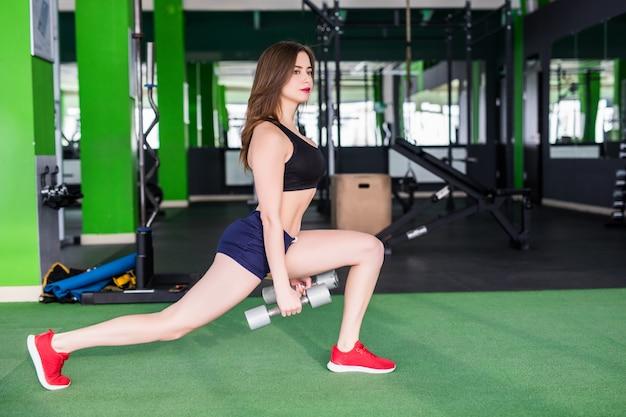Deportiva mujer con cuerpo en forma fuerte está haciendo diferentes ejercicios en el moderno club deportivo con espejos