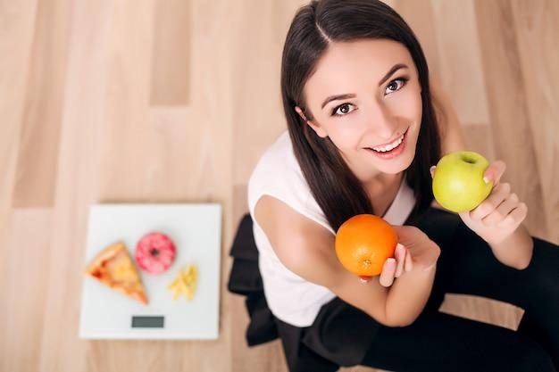Deportiva mujer con escala y manzana verde y naranja