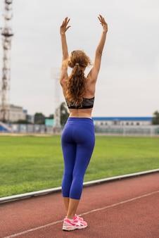 Deportiva mujer en estadio con manos levantadas