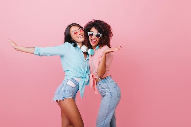 Deportiva mujer europea con piel bronceada bailando con alegre amigo africano. felices dos chicas en atuendos de verano jugando juntas.