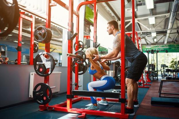 Deportiva mujer haciendo ejercicios con pesas con la ayuda de su entrenador personal en el gimnasio