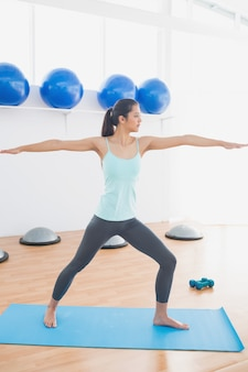 Deportiva mujer joven estirando las manos en el gimnasio