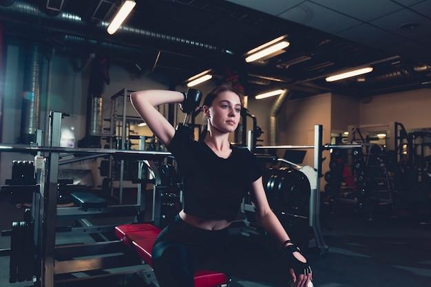 Deportiva mujer joven haciendo ejercicio con pesas en el gimnasio