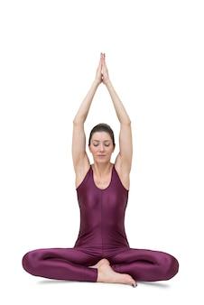 Deportiva mujer joven haciendo prácticas de yoga aisladas sobre fondo blanco