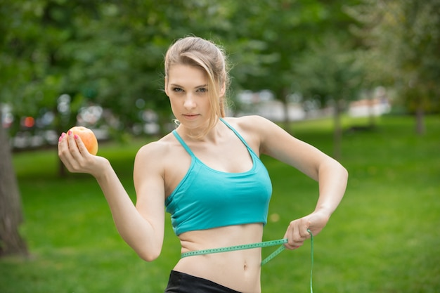 Deportiva mujer joven con manzana y cinta métrica
