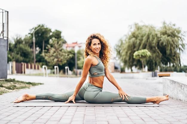 Deportiva mujer joven con el pelo largo en chándal gris haciendo ejercicios de estiramiento en la calle