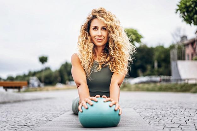 Deportiva mujer joven con pelo largo y rubio y rizado haciendo ejercicios de estiramiento con una pelota especial en la calle.